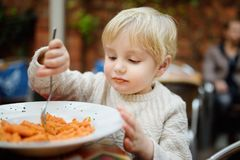 Cute toddler boy eating pasta in Italian indoors restaurant. Healthy/unhealthy food for little kids royalty free stock photography