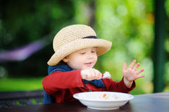 Cute toddler boy eating rice cereal outdoors. Healthy food for little kids Royalty Free Stock Photography