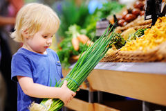 Cute toddler boy in a food store choosing fresh organic green onion Stock Image