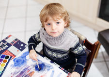 Cute toddler boy having fun indoor, painting with different pain Royalty Free Stock Images