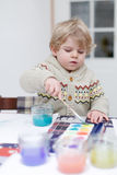 Cute toddler boy having fun indoor, painting with different pain Royalty Free Stock Photos