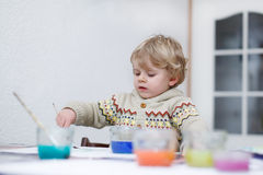 Cute toddler boy having fun indoor, painting with different pain Royalty Free Stock Image