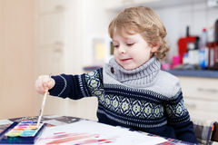 Cute toddler boy having fun indoor, painting with different pain Stock Photos