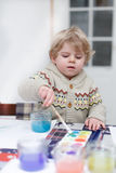 Cute toddler boy having fun indoor, painting with different pain Stock Images