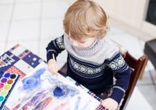 Cute toddler boy having fun indoor, painting with different pain Stock Image