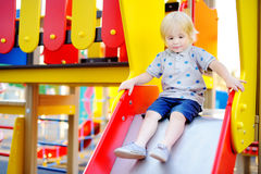 Cute toddler boy having fun on slide on playground. Active outdoors game for little children Stock Photography