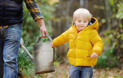 Cute toddler boy helping his father watering plants Royalty Free Stock Photography