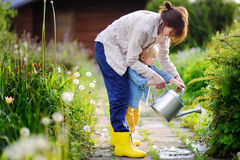 Cute toddler boy and his young mother watering plants in the garden. At summer sunny day Royalty Free Stock Image