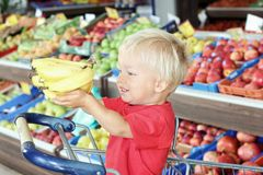 Cute toddler boy holds bananas in his hands while sitting in shopping cart inside supermarket stock images