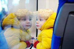 Cute toddler boy looking out train window outside, while it moving. Going on vacations and traveling by railway Royalty Free Stock Image
