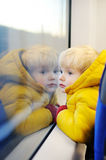 Cute toddler boy looking out train window outside. While it moving. Going on vacations and traveling by railway Royalty Free Stock Photo