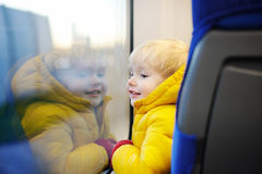 Cute toddler boy looking out train window outside, while it moving. Going on vacations and traveling by railway Royalty Free Stock Images
