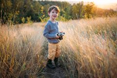 Cute toddler boy with old retro vintage camera on autumn grass background. Child with curly hair and grey coat playing royalty free stock image
