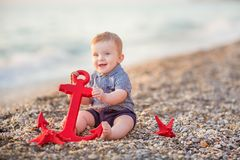 Cute toddler boy playing on the beach with sea red star and anchor. Cute toddler boy playing on the beach royalty free stock images