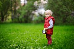 Cute toddler boy playing outdoors at cold summer or spring day. Fashion seasonal clothing. Child with toy lantern Stock Photos