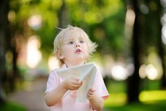 Cute toddler boy playing with paper plane in a summer park. Outdoors child leisure. Game for little kid Stock Images
