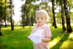 Cute toddler boy playing with paper plane in a summer park. Outdoors child leisure. Game for little kid Stock Photos