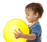 Cute toddler boy is playing with yellow balloon Stock Image
