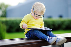 Cute toddler boy reading a book outdoors Stock Images