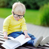 Cute toddler boy reading a book outdoors on warm summer day Royalty Free Stock Images