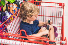 Cute toddler boy sitting in the shopping cart in a food store or. A supermarket Stock Images