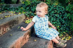 Cute toddler boy sitting on the stairs Royalty Free Stock Photo