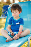 Cute toddler boy sitting on a sunbed Royalty Free Stock Photos