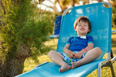 Cute toddler boy sitting on a sunbed Royalty Free Stock Images