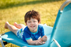 Cute toddler boy sitting on a sunbed Stock Photos