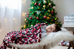 Cute toddler boy, sleeping in a big chair in front of the christ Stock Images