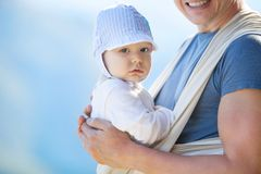 Cute toddler boy in sling, father carrying son Royalty Free Stock Images
