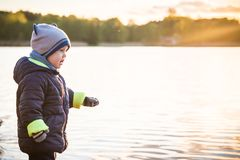 Cute toddler boy in spring clothes near water. At sunset time royalty free stock images