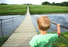 Cute toddler boy on a suspension bridge across the river. Adventure travel, look into the future, opening a new way concept.  Stock Images