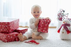 Cute toddler boy, sweet baby, opening presents at home royalty free stock photo
