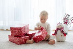 Cute toddler boy, sweet baby, opening presents at home stock image