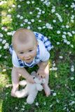 Cute toddler boy with teddy bear, sitting on the grass, daisies Stock Photo