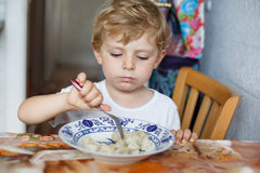 Cute toddler boy of three years eating pasta at home kitchen Royalty Free Stock Photography