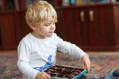 Cute toddler boy of two years eating chocolate Royalty Free Stock Photography