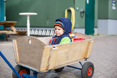 Cute toddler boy of two years in wooden trolley in autumn clothe Royalty Free Stock Image