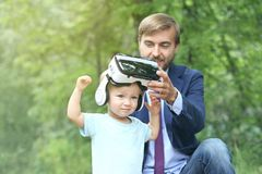 Cute toddler boy with virtual reality glusses outdoor. Father helps his toddler son to put on vr glasses. Future Technology Concep. T. Copy space stock photos