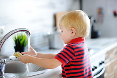 Cute toddler boy washing dishes in domestic kitchen Stock Image