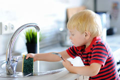 Cute toddler boy washing dishes in domestic kitchen Stock Photos