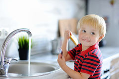 Cute toddler boy washing dishes in domestic kitchen Stock Photo