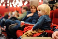 Cute toddler boy watching cartoon movie in the cinema royalty free stock photo