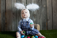 Cute toddler boy wearing bunny ears playing   with  Easter eggs Royalty Free Stock Images