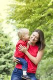 Cute toddler boy whispers in the mother`s ear. Kid kisses mom on the cheek. Very emotional mom and baby. Family look clothing. Co Royalty Free Stock Photo