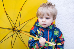 Cute toddler boy with yellow umbrella, outdoors Royalty Free Stock Photo