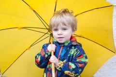 Cute toddler boy with yellow umbrella, outdoors Stock Photos