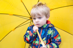 Cute toddler boy with yellow umbrella, outdoors Royalty Free Stock Photography
