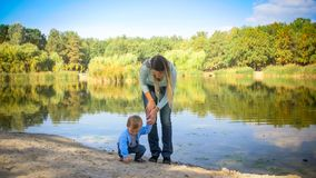 Cute toddler boy with young mother near lake at park. Toddler boy with young mother near lake at park Royalty Free Stock Image